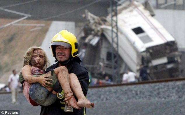Rescue: A fireman carries a wounded victim from the wreckage of the train crash near Santiago de Compostela