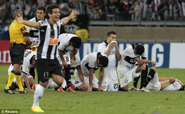 Mixed emotions: Mineiro players celebrate the winning penalty while Olimpia look on