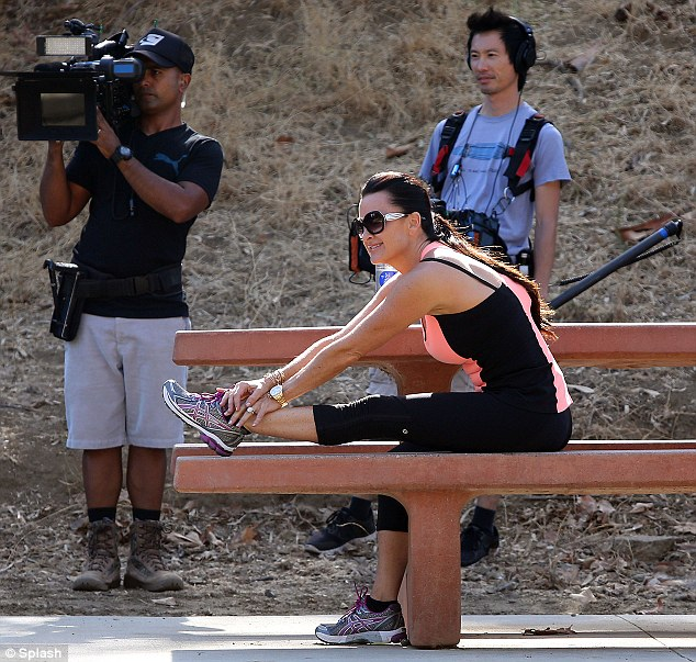 Smart stretcher: Kyle took care of her muscles by stretching her legs out on a bench
