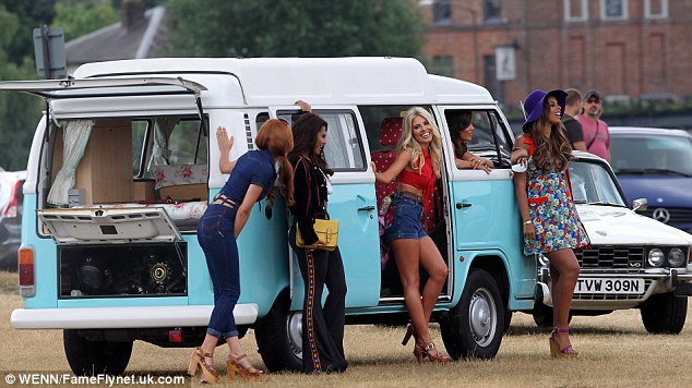 Hanging out: The group giggled away as they filmed beside the blue camper van in what looks set to be a Seventies inspired video