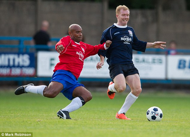 Old rivals: Trevor Sinclair dives in to tackle Scholes