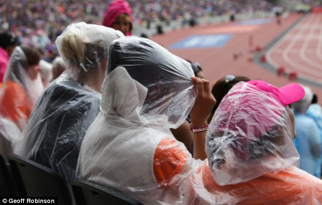 Washout: Spectators at London's Olympic stadium were caught in heavy showers yesterday watching stars from last year's Games compete
