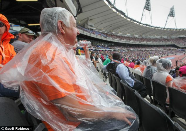 Rainy spell: Crowds at the Olympic Park in East London sit through the wet weather, hoping the showers will pass