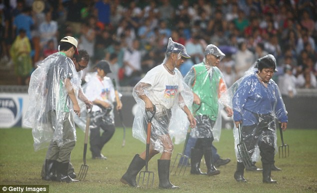 Dampen spirits: The match was blighted by horrendous weather and therefore a badly cut up pitch