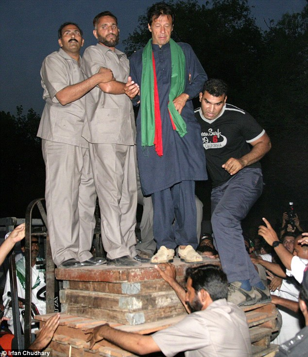 Khan is lifted on to a stage: Politician leader Imran Khan pictured being lifted by guards and party members onto a forklift at an election rally in Lahore, Pakistan, in May