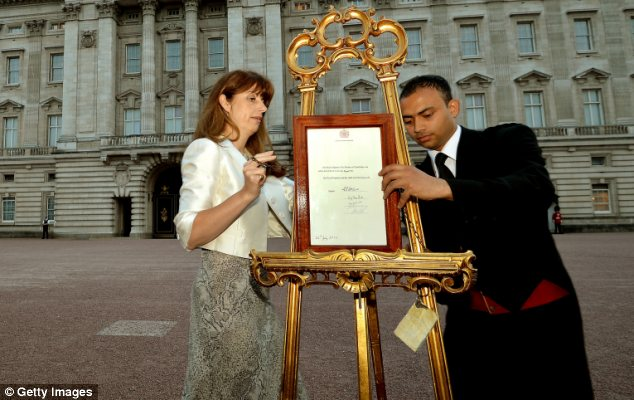 Footman Badar Azim with the Queen's Press Secretary Ailsa Anderson holding the announcement of Prince George's birth