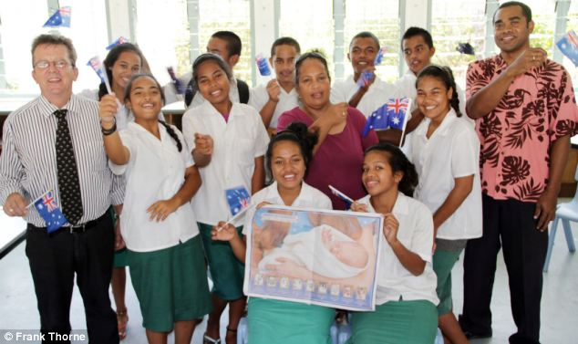 Poster boy: Students and teachers at Nauru College cheering the birth of Prince George
