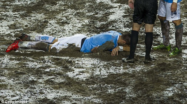 Face down: Negredo lies in the mud after taking a knock