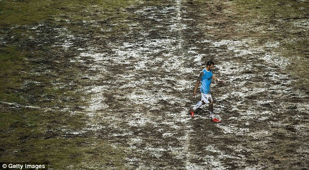 Mud party: Alvaro Negredo trudges across the tattered pitch