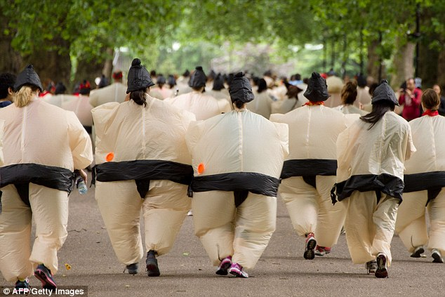 Fun day out: Participants take part in the annual 5km Sumo Run in west London today