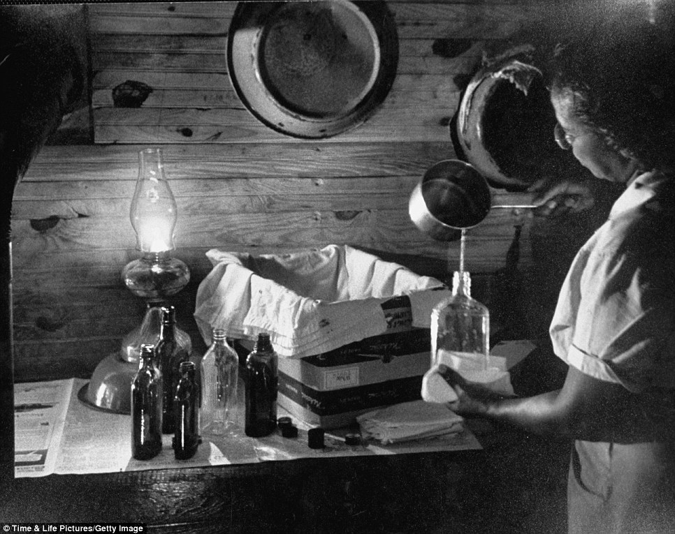 Maude Callen preparing a solution in front of an incubator made from a box and whiskey bottles full of warm water