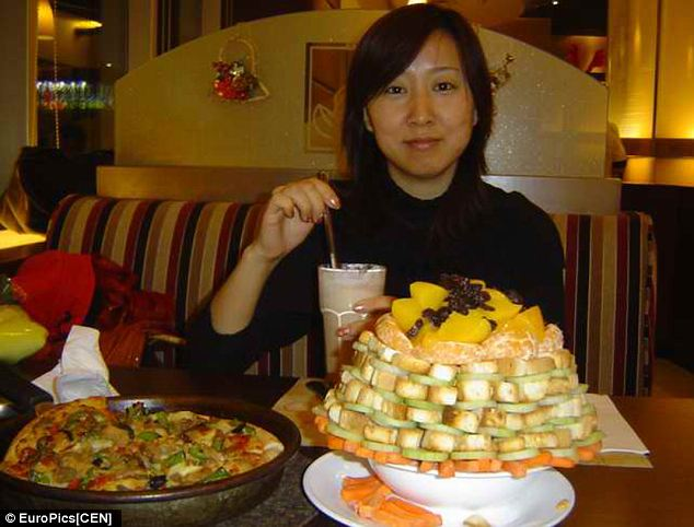 A proud stacker poses with her creation, which appears to include quite a few blocks of tofu