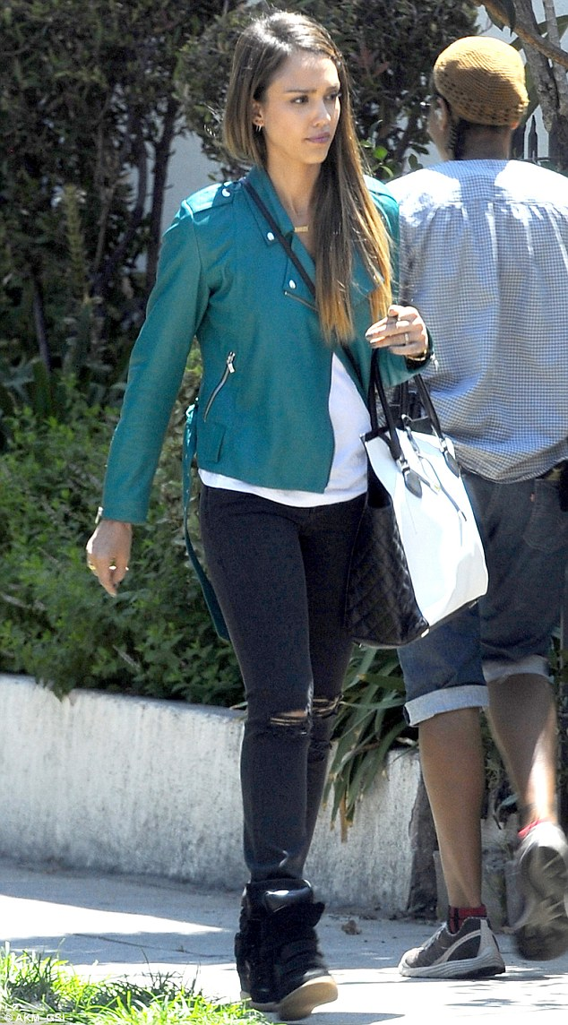 Going green: Jessica wore a white shirt teamed with a green leather jacket, skinny torn jeans and high top wedge sneakers on set