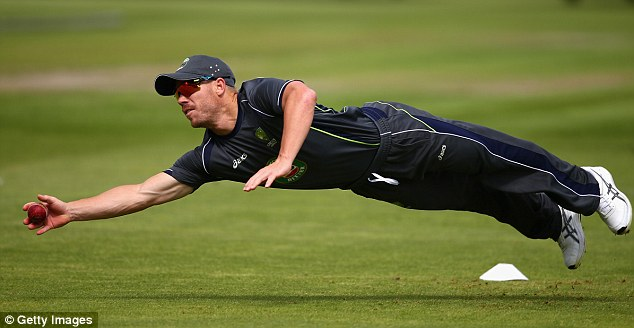Back in the frame: David Warner diving full stretch during fielding practice at Australia's net session on Monday