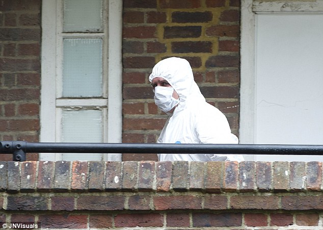 Probe: A forensics officer is seen outside the property where a 28-year-old woman was stabbed to death