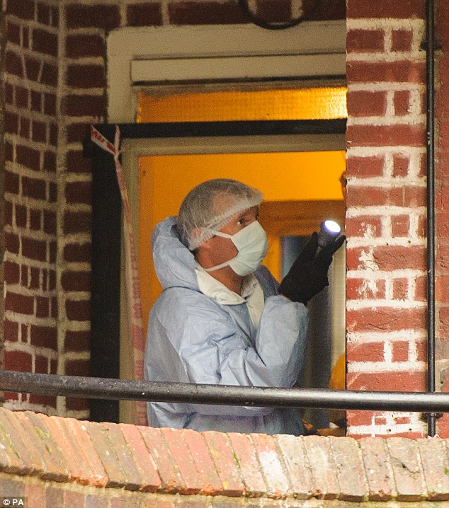 Probe: A forensics officer examines the property where a 28-year-old woman was stabbed to death