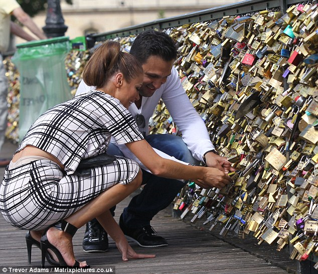 Locked in love: The couple grinned as they added their own lock to the Lover's Bridge in the French capital