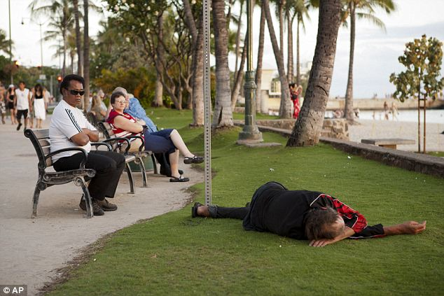 Aloha: A man sleeps near Waikiki Beach, in 2011 in Honolulu. The state of Hawaii is poised to begin is 'return-to-home' program, which will give eligible homeless people one-way tickets back to the families on the mainland