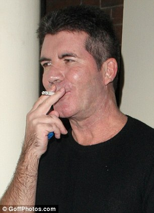 Nicotine fan: Cowell is regularly seen puffing away on a nicotine stick