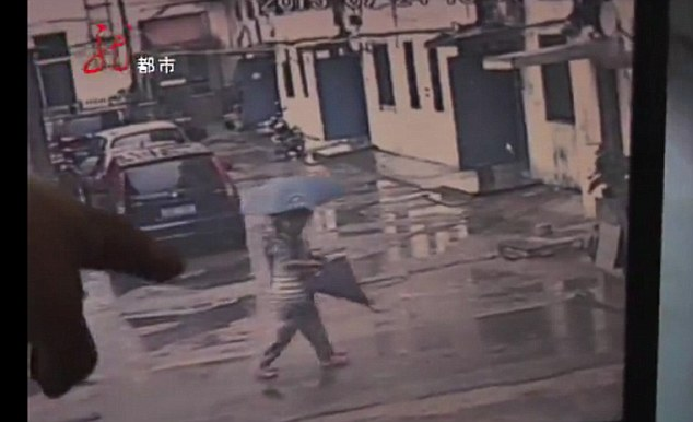 Last moments: This CCTV footage reportedly shows Hu walking with the pregnant woman under an umbrella to the expectant mother's house after stopping in the street to help her