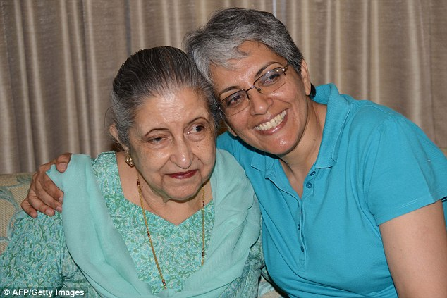 Long battle: Ms Kaur smiles for the camera with her daughter Gurveen at her home in Chandigarh today, after a court ruled the former Maharajah's daughters should inherit his estate