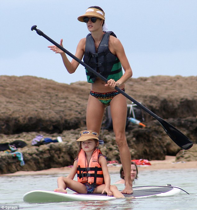Matching: Perched on her mother's board, the little five-year-old wore an identical straw visor to the Brazilian born beauty