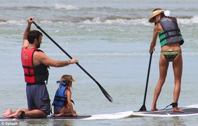 Helping hand: The businessman hopped on the same board as his daughter while Alessandra jumped on another one