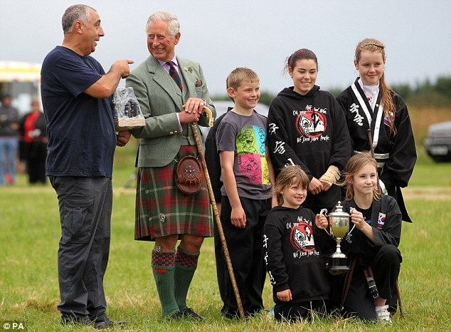 The Prince of Wales has his picture taken with the winning tug of war team after judging the competition