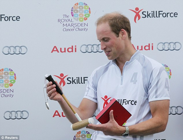 Delighted: Prince William admires the child's polo mallet he was presented at the charity match