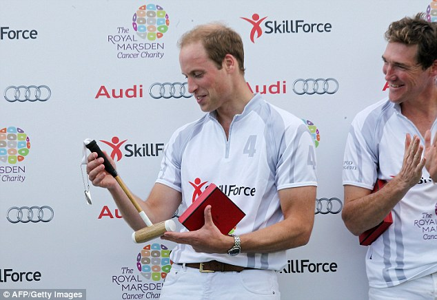 The Duke of Cambridge looks fondly at the polo mallet he was presented for his son Prince George