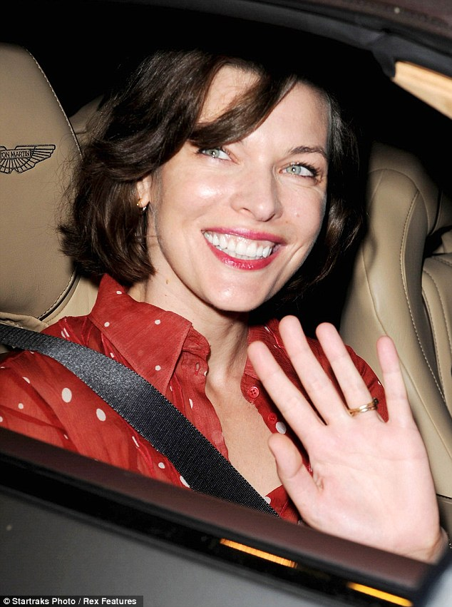So friendly: The green-eyed star waved to onlookers as she was driven away by Paul