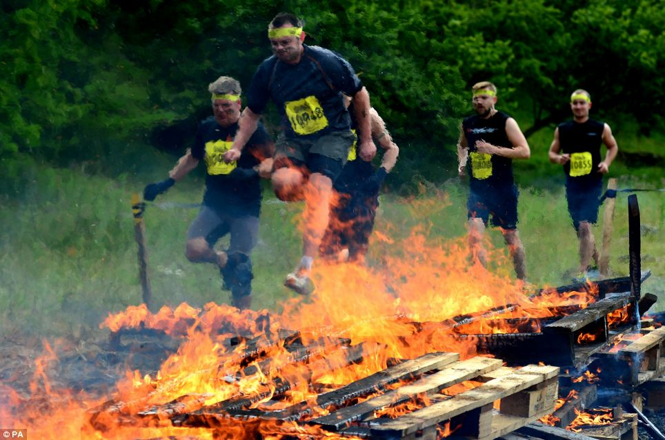 Chargrilled: Competitors jump through flames in the 'Human BBQ' section of the challenge