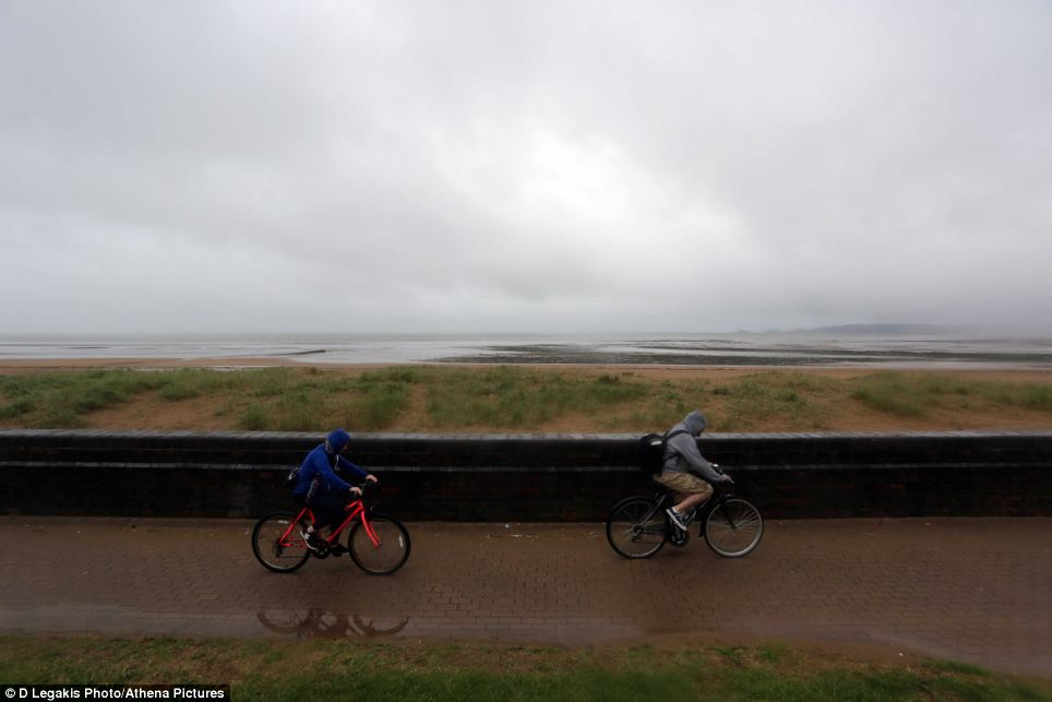 British summer: Cyclists brave the miserable weather in Swansea, south Wales