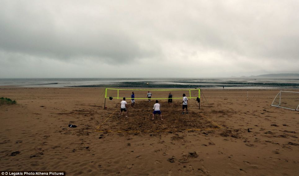 Determined: Volleyball players remain intent on having a good time despite the inclement weather in Swansea