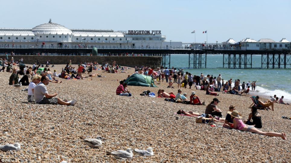 Warm: There was better weather in Brighton where sunbathers gathered on the beach, although far fewer than in recent weeks