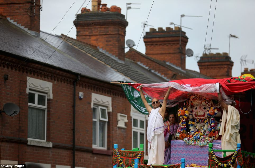 Grey skies: The Rathayatra procession winds through the streets of Leicester. The festival sees the figures of Lady Suhadra, Lord Jagannatha and Lord Balaram drawn in hand pulled chariots as people sing and chant