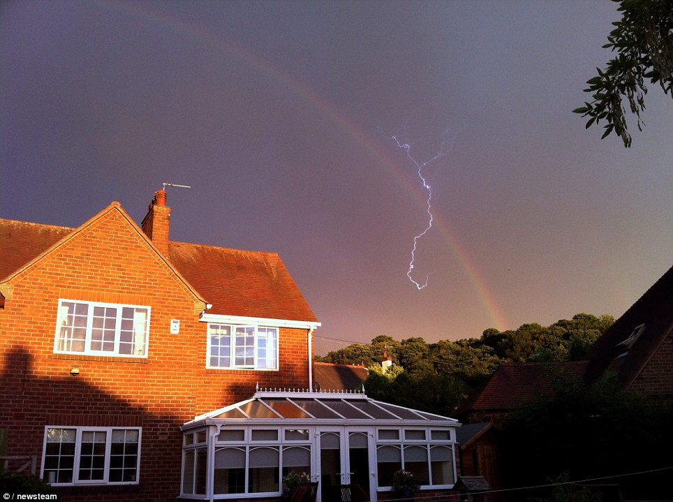 Magic: As Britain;s weather stays unsettled, this is the spectacular moment a photographer struck gold by capturing a bolt of lightning cracking through a rainbow