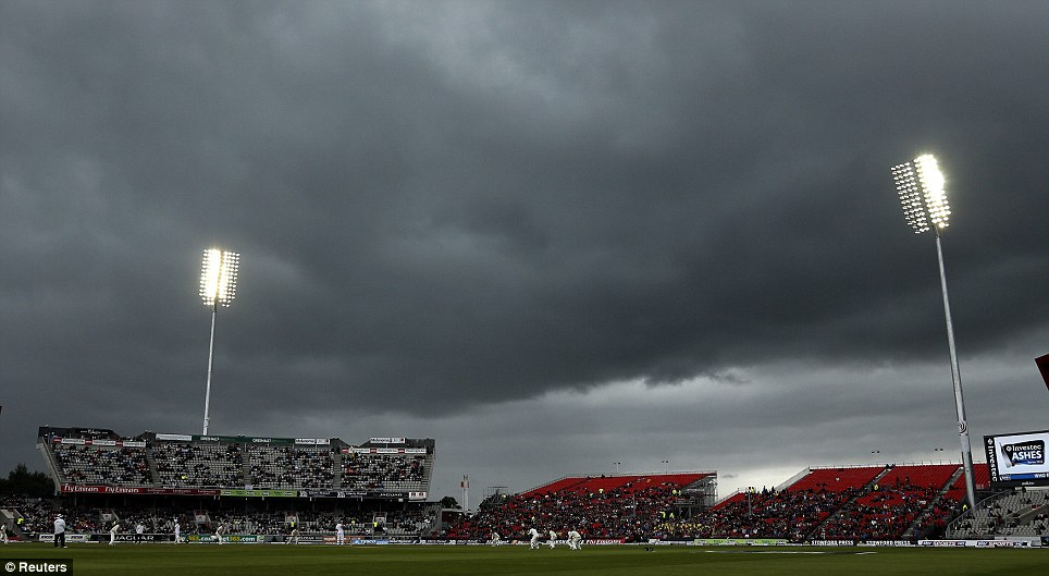 Ominous: Australia's Peter Siddle bowls to England's Joe Root under dark skies on the final day of the third Ashes test match at Old Trafford cricket ground in Manchester