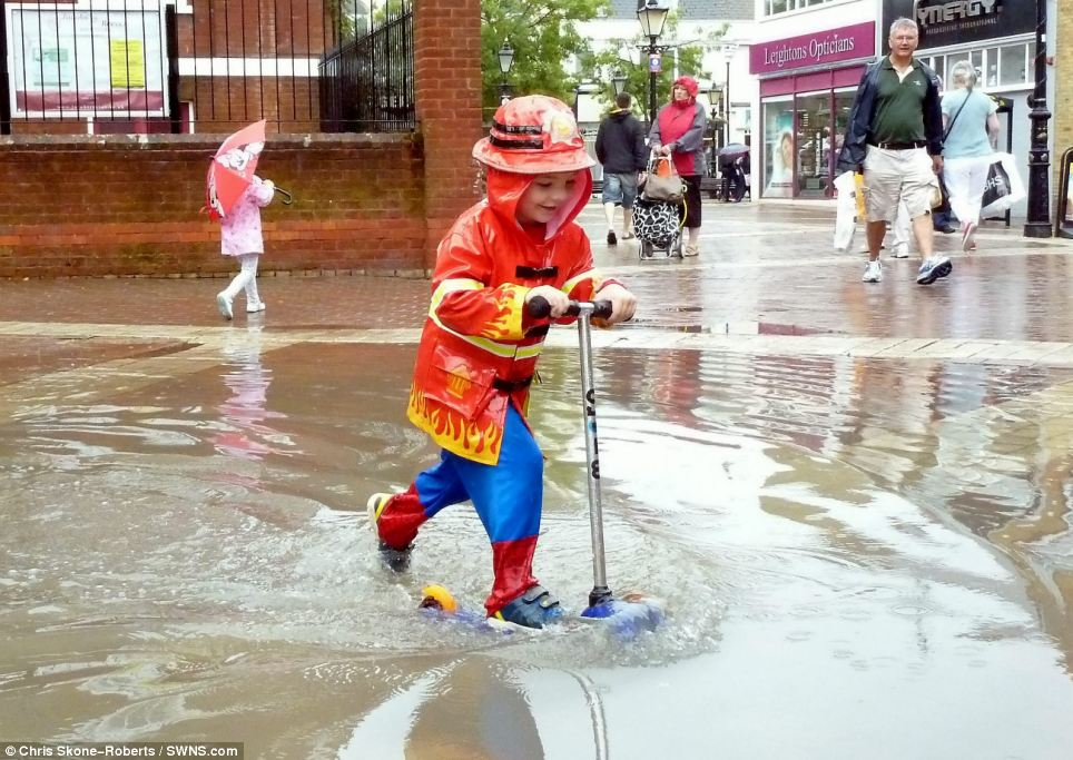 At least someone's having fun! Four-year-old Finley Reynolds from Poole in Dorest splashes through a puddle in his fireman outfit and scooter