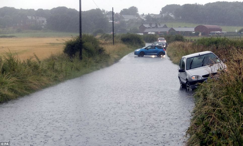 Time to turn back: Drivers near Shiremoor on North Tyneside decide not to risk it and turn around when they reach a road of deep water where a car has been abandoned