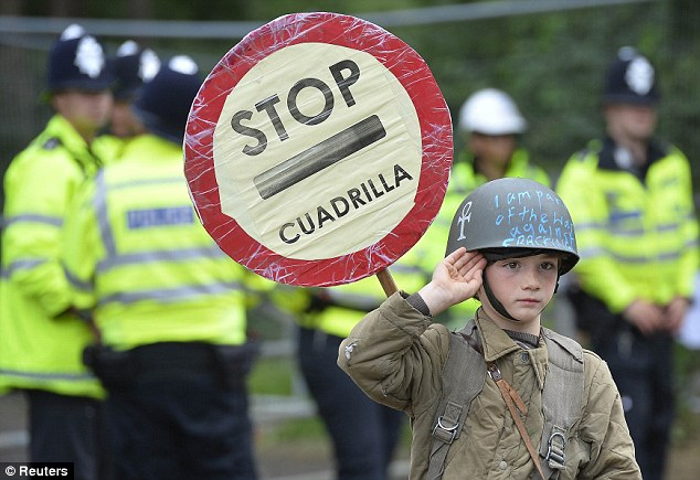 Protestor Rory Rush, aged seven, poses in front of police officers protecting the entrance gate of the site run by Cuadrilla Resources