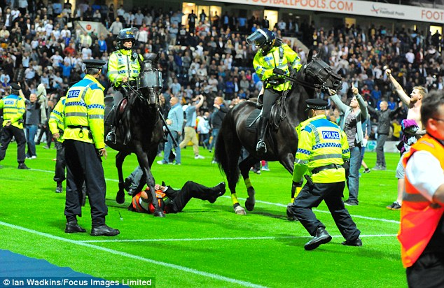 Ugly scenes: A steward was trampled by a police horse as Preston fans invaded the pitch. TV images showed that he was unharmed