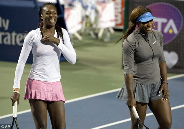 Family affair: Venus (left) and Serena Williams have a laugh as the Toronto crowd get their money's worth