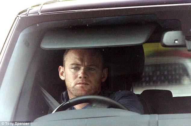 Here he is: Wayne Rooney pictured arriving at Manchester United's Carrington training ground on Tuesday