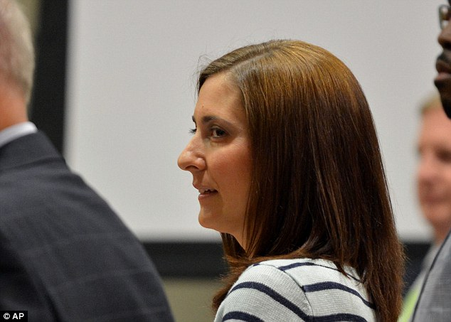 Accused: Andrea Sneiderman smiles as the jury comes into the Dekalb County Superior Court before opening statements were given by attorneys