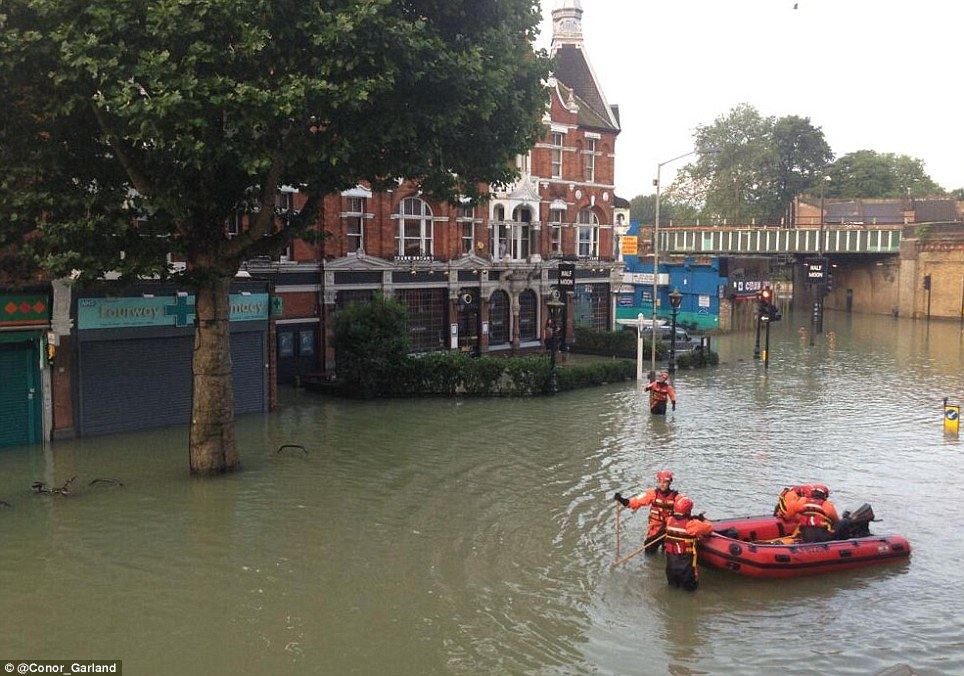 Boat rescue: Firefighters in a boat on Herne Hill this morning after a water main burst