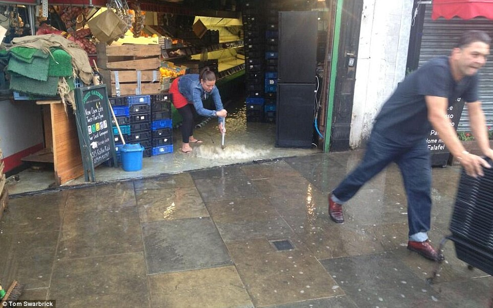 Working hard: Herne Hill's greengrocers is forced to remove water from its shop after water began pouring in this morning