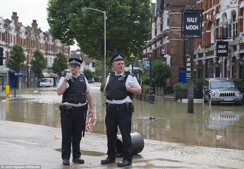 Standing guard: Police as well as other members of the emergency services in London were called to Herne Hill to ensure its residents are safe