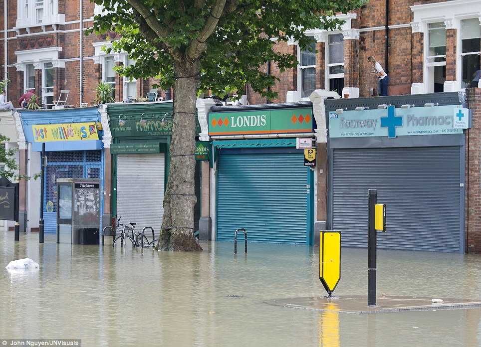 Stuck: People stand on their rooftops in the south London suburb as they are hemmed in by the water, which was up to a metre high in some areas