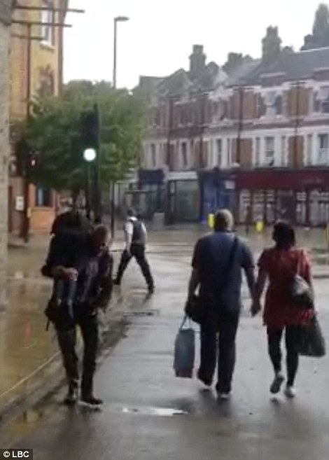 A man helps a lady through the water on Half Moon Lane in Herne Hill